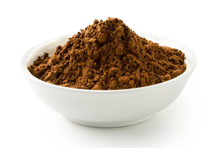 Cocoa powder in a white ceramic bowl isolated on white.