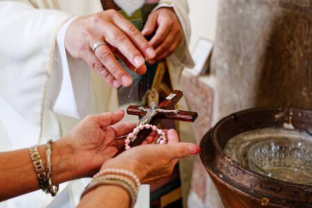 Un sacerdote bendiciendo el rosario y el crucifijo con agua bendita. Foto de archivo
