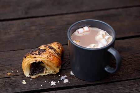 Hot chocolate with marshmallows in a blue-grey ceramic mug next to a half of chocolate croissant isolated on rustic dark brown wood table. 写真素材