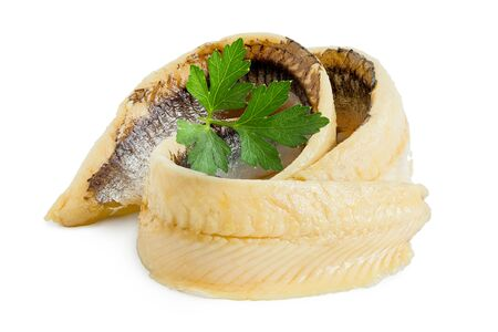 Two rolled anchovy fillets with flat leaf parsley isolated on white. Stock Photo