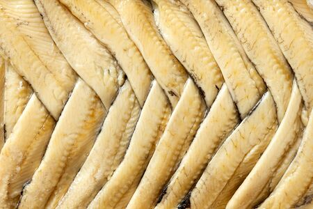Background of anchovy fillets in oil arranged in herringbone pattern from above. Closeup.