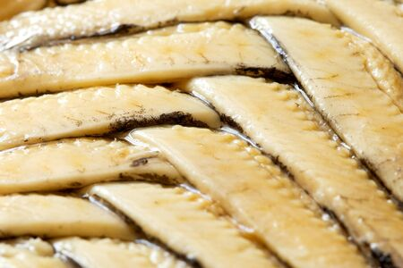 Background of anchovy fillets in oil arranged in herringbone pattern. Closeup. Stock Photo