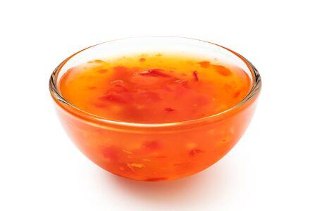 Sauce chili douce dans un bol en verre isolé sur blanc.