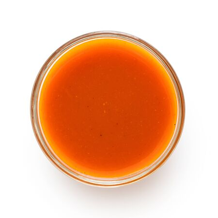 Peri peri chilli sauce in a glass bowl isolated on white from above.