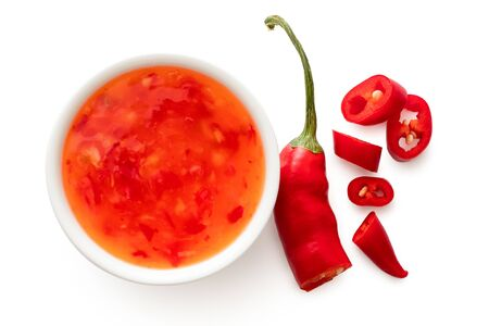 Sweet chilli sauce in a white ceramic bowl next to a cut up chilli pepper isolated on white from above. Zdjęcie Seryjne