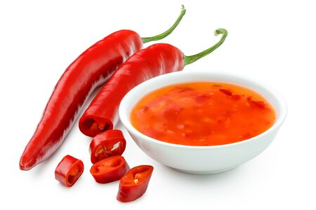 Sweet chilli sauce in a white ceramic bowl next to one whole and one cut red chilli isolated on white.