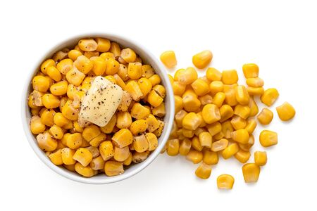 Canned sweet corn with a knob of butter and ground black pepper in a white ceramic bowl next to spilled sweet corn isolated on white. Top view.