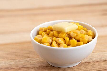 Maïs sucré en conserve avec une noix de beurre dans un bol en céramique blanche isolé sur bois clair. Espace pour le texte.