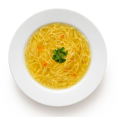 Instant chicken noodle soup in a white ceramic soup plate isolated on white. Top view. Parsley garnish.