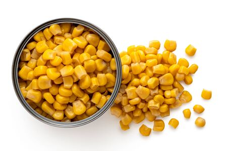 Canned sweet corn in an open metal tin next to spilled sweet corn isolated on white. Top view.