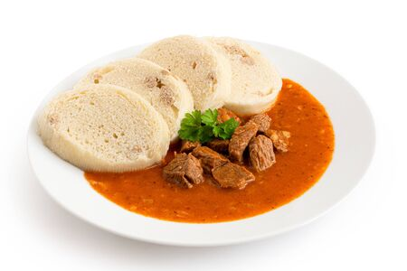 Beef goulash with bread dumplings and parsley garnish on white ceramic plate isolated on white.