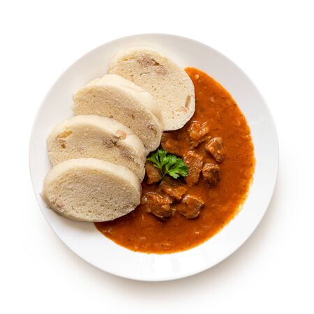 Beef goulash with bread dumplings and parsley garnish on white ceramic plate isolated on white. Top view.