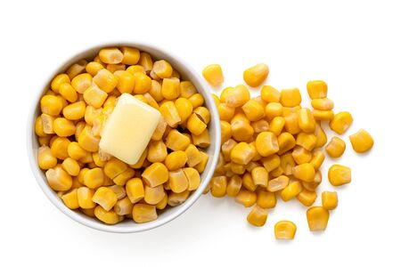 Canned sweet corn with a knob of butter in a white ceramic bowl next to spilled sweet corn isolated on white. Top view. Banco de Imagens