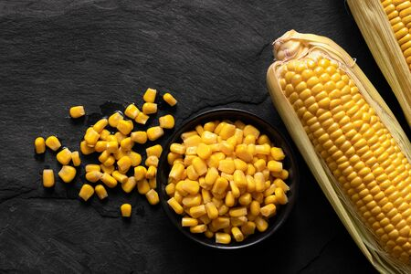 Canned sweet corn in a black ceramic bowl next to two corn cobs in husks and spilled corn on black slate. Top view.  Banco de Imagens