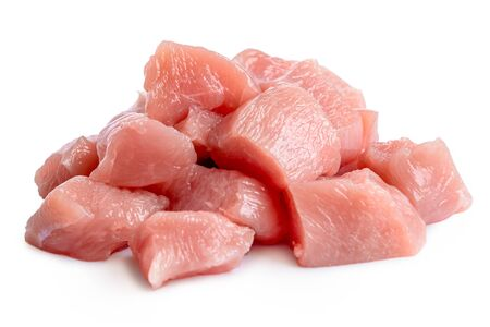A pile of cut up uncooked boned chicken breast isolated on white.