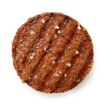 Gegrilltes Burger-Patty auf Pflanzenbasis mit Grillspuren und Steinsalz, isoliert auf weiss. Ansicht von oben.
