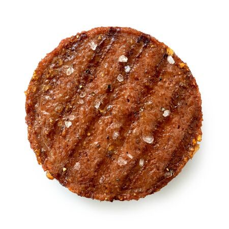 Plant based grilled burger patty with grill marks and rock salt isolated on white. Top view.