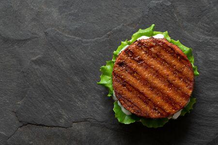 Empanada de hamburguesa a base de plantas recién asada en pan con lechuga y salsa aislado en pizarra negra. Vista superior. Copie el espacio.