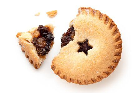 Aufgebrochener traditioneller britischer Weihnachtsmince Pie mit Fruchtfüllung isoliert auf weiss. Ansicht von oben.