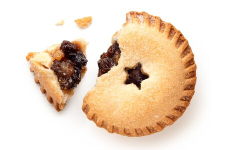 Broken open traditional british christmas mince pie with fruit filling isolated on white. Top view.