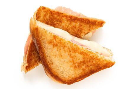 Sándwich clásico tostado de queso y jamón cortado por la mitad aislado en blanco. Vista superior.
