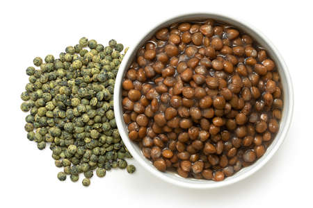 Cooked french green puy lentils in white ceramic bowl next to dry lentils isolated on white. Top view. Zdjęcie Seryjne