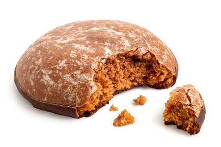 Glazed gingerbread lebkuchen with chocolate isolated on white. Bite missing with crumbs. Standard-Bild