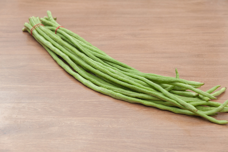 close up of Yard long Bean on wooden table Stock Photo