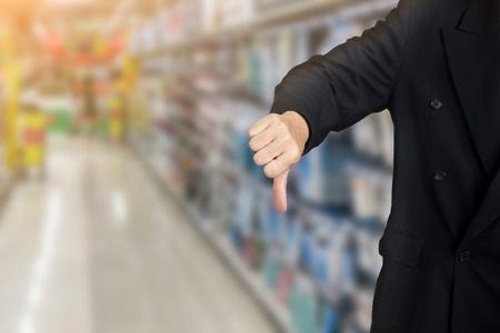 businessman give bad thumbs down on supermarket background Stok Fotoğraf