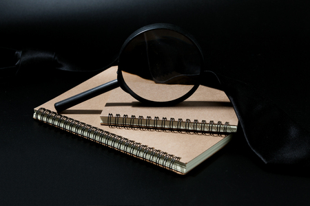 magnifying glass and notebook on black background, investigate concept Stock Photo