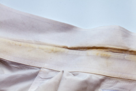 Yellow collar stain on white dirty shirt