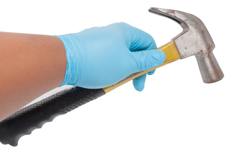 hand in blue glove holding a hammer Stock Photo