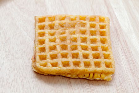 close up of waffle with corn on wooden plate