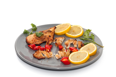 Roast chicken with chilli, lemon on grey plate