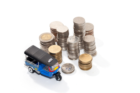 Thai traditional tuk tuk toy and coin on white background