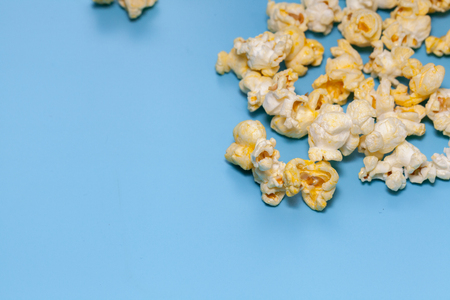 close up of popcorn in wooden on blue background