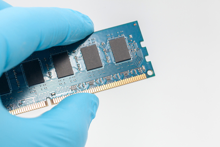 hand in blue glove holding ram memory on white background Stock Photo