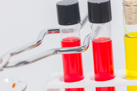 close up of Test Tube Holder holding red liquid Stock Photo