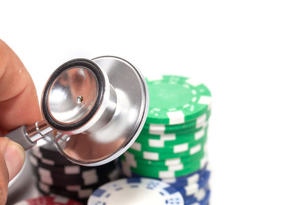 stethoscope and pile of casino chips on white background