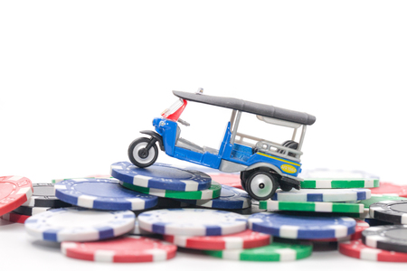 pile of casino chips and tuk tuk taxi on white background