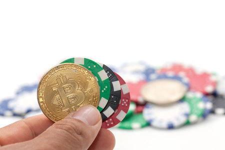 hand holding bitcoin and pile of casino chips on white background