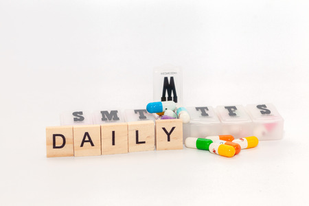 word daily with colorful pill on white background stock photo