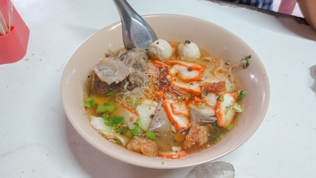 bowl of spicy tom yum noodle soup with pork in Thai style Stock Photo
