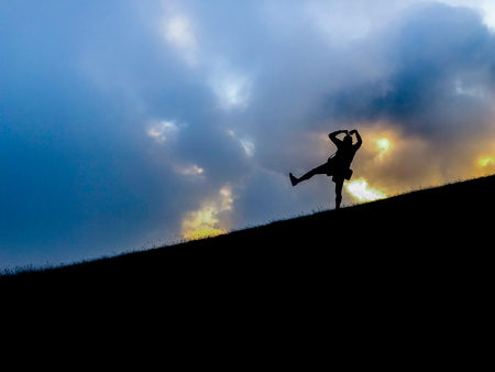 silhouette of tourist hiker acting on top of mountain
