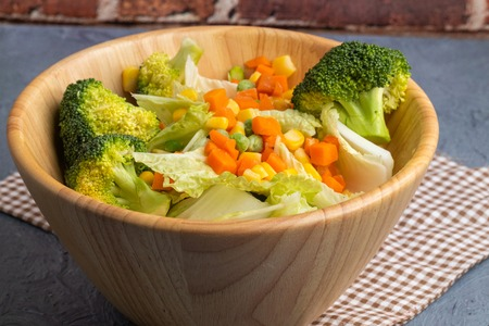 carrots corns broccoli and peas on wooden bowl Stockfoto