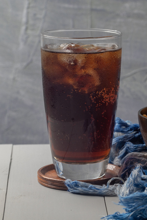 close up of iced cola in glass on the table