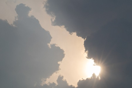 the sun hide behind grey cloud at evening