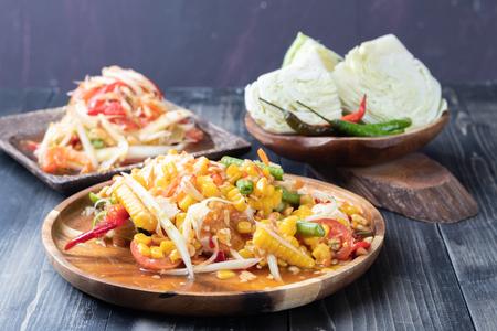 Ensalada de maíz y papaya en placa de madera estilo tailandés
