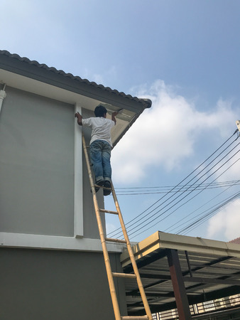 worker fixing crack ceiling and roof of the house Stock Photo