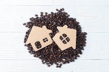 close up of pile roast coffee beans and small wooden home